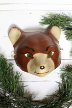Old Vintage Retro Papier Mache Unusual Mask Of Bear Of Fox On White Wooden Background With Fur Tree Frame. Merry Christmas And Happy New Year 2021 Postcard/poster Design. Masquerade Or Ball Invitation