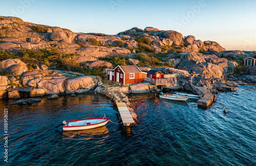 Aerial view of a small bay with red boat houses and boats in Hönö, Gothenburg Archipelago, Sweden, Scandinavia