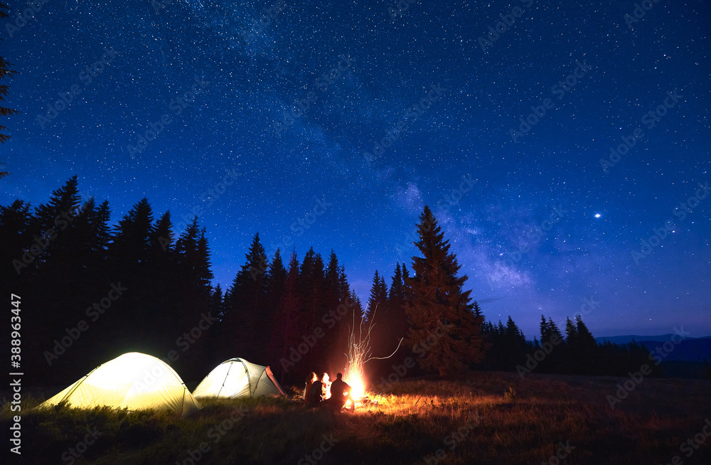 Fototapeta Evening camping with campfire. People having a rest near tent city, enjoying valley of mountains in pine forest. Dark blue night sky is strewn with bright stars and Milky Way is visible on it. - obraz na płótnie