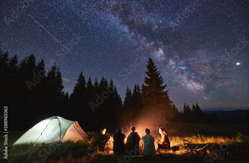 Obraz Evening summer camping, spruce forest on background, sky with falling stars and milky way. Group of five friends sitting together around campfire in mountains, enjoying fresh air near illuminated tent - fototapety do salonu