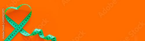 Obraz Green metric measuring tape on horizontal orange background. Mockup for body slimming, weight loss - fototapety do salonu