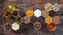 Spices In Hexagonal Jars On A Wooden Surface