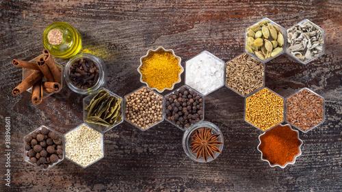 Fototapeta Spices in hexagonal jars on a wooden surface obraz
