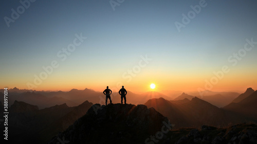 Obraz Two Men reaching summit enjoying freedom and looking towards mountains sunset. - fototapety do salonu