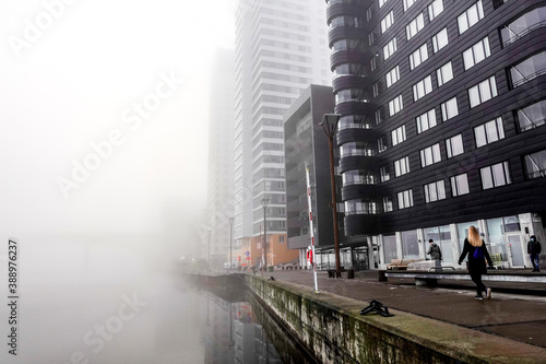 Photo Stockholm, Sweden A woman walking in the morning fog at Liljeholmskajen