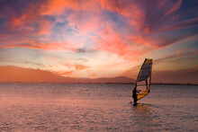 Windsurfer Riding On A Surfboard Against A Cloudy Orange Sunset. Empty Copy Space For Editor's Content.