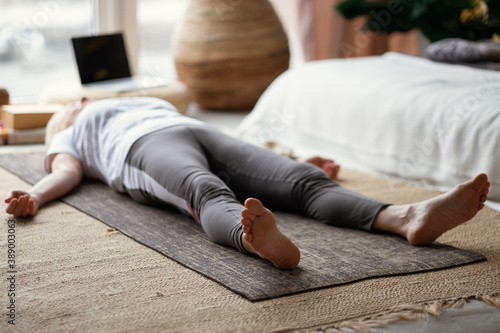 Foto Senior caucasian woman lying on yoga mat after workout