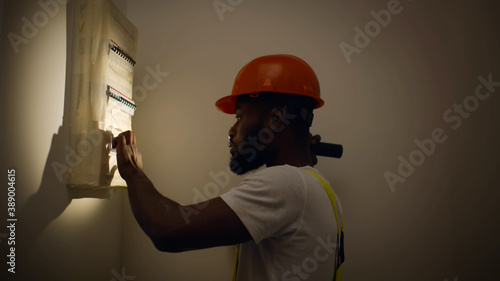 African electrician with flashlight examining electrical box with pliers in new Canvas Print