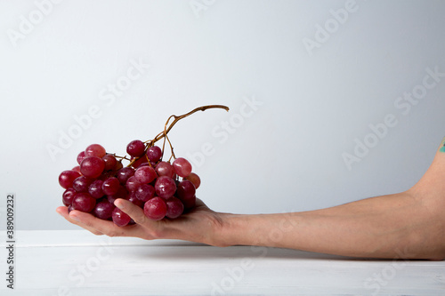Foto still life of red grapes on white wooden table