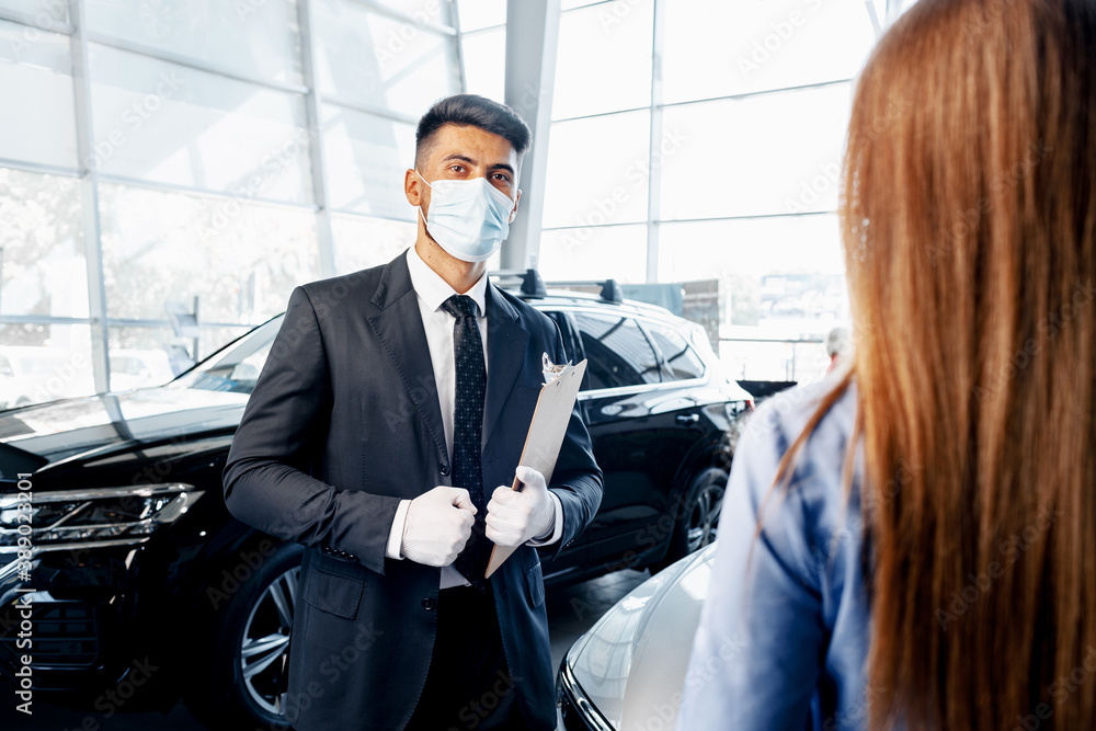 Fototapeta Man car salesman in face mask talking to a client in showroom