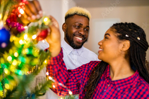 multicultural family decorating christmas tree with ball and garland Canvas