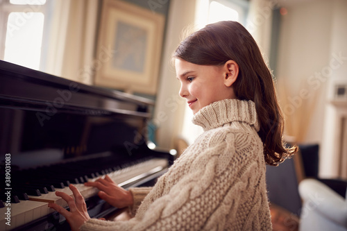 Fényképezés Young Girl Learning To Play Piano Practising At Home