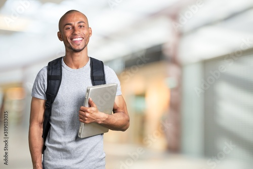 Canvas Print Smiling young black college student with laptop