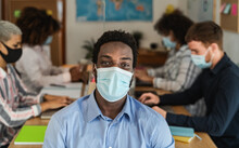 African Man Wearing Face Mask In Co-working Creative Space With Team Work - Young People Working During Corona Virus Pandemic
