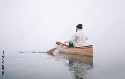 Cuadros en Lienzo Rear view of man paddling canoe in the winter, copy space