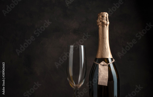 Fototapeta A bottle of alcohol and a wine glass on a brown background with space for copying. Concept of holiday backgrounds. obraz