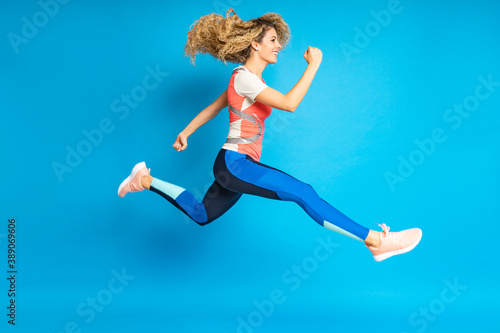 Tela young and blonde athlete woman running and jumping in motion on isolated backgro