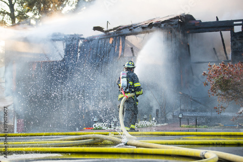 Fotografia, Obraz A residential home burns in a house fire as firefighters spay water from a hose in an effort to put it out
