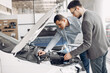 Man buying the car. Businessman in a car salon. Assistant with a client