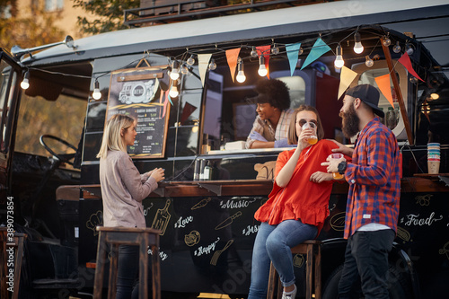 Fototapeta people socializing in front of truck food, drinking juices, talking obraz