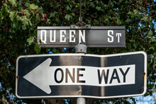Queen Street Sign With A Bent One Way Sign Pointing To The Left Below It