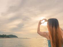 Hands Making Heart Shape Toward The Sky With Sunlight, Sun Reflection On Surface Of The Sea Growing Like Sparkling Diamond, Golden Skycap Scenery In Summer Time, Eco Tourism Love Environment Concept.