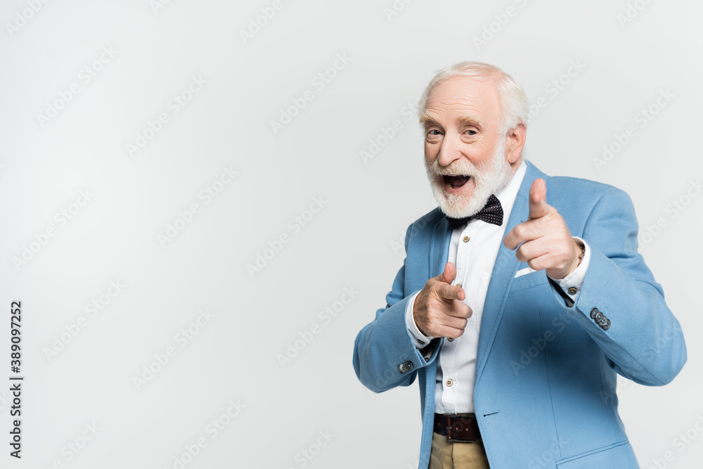 Fototapeta Excited senior man in bow tie pointing with fingers at camera isolated on grey