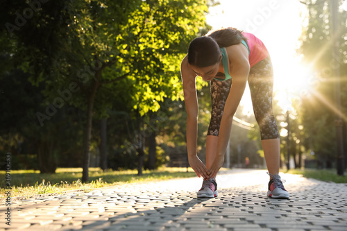 Fototapeta Young woman stretching before morning run in park. Space for text