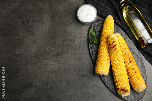 Fresh grilled corn cobs on grey table, flat lay. Space for text Canvas