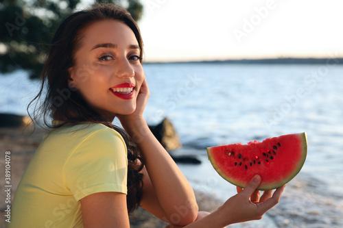 Obraz Beautiful young woman with watermelon near river - fototapety do salonu
