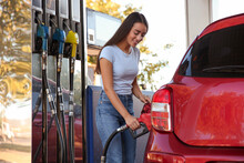 Young Woman Refueling Car At Self Service Gas Station
