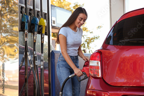 Fototapeta Young woman refueling car at self service gas station