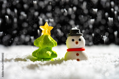 Cuadros en Lienzo snowman and Christmas tree in a snowing night