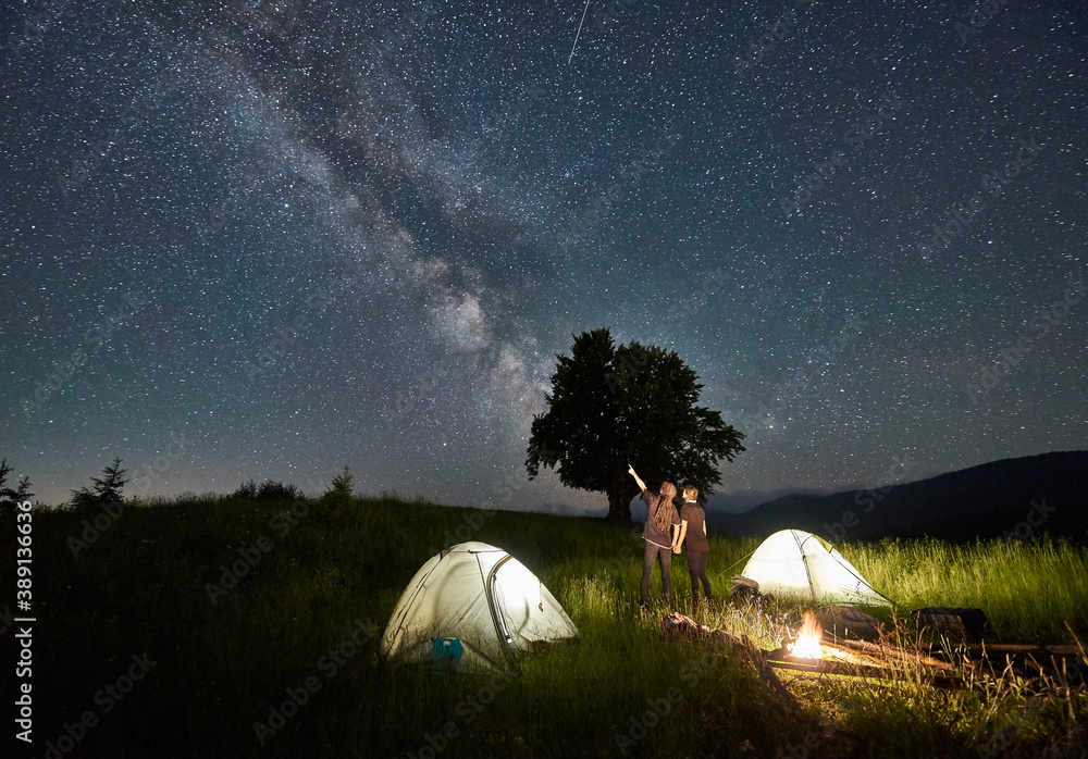 Fototapeta Man hiker with girlfriend pointing at Milky Way on majestic starry sky. Couple in love standing near illuminated camp tents, looking at sky with stars. Concept of hiking, night camping, relationships