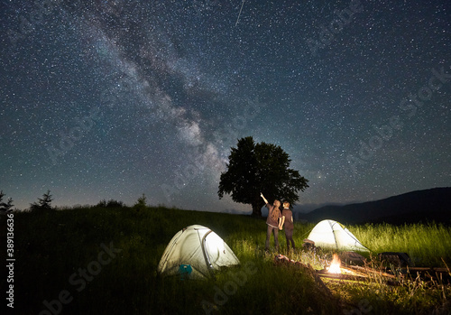 Obraz Man hiker with girlfriend pointing at Milky Way on majestic starry sky. Couple in love standing near illuminated camp tents, looking at sky with stars. Concept of hiking, night camping, relationships - fototapety do salonu