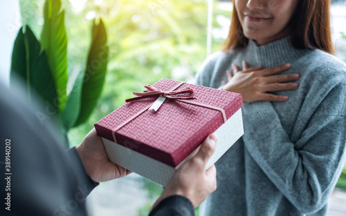 Fototapeta A boyfriend surprising and giving his girlfriend a gift box