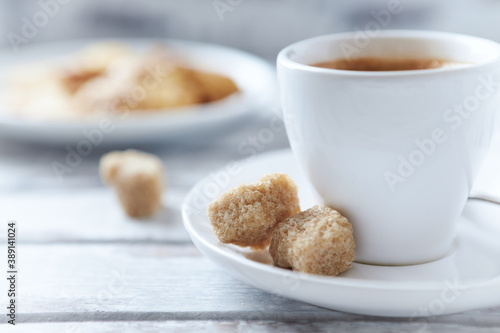 Obraz na plátně Cup of coffee and brown sugar cubes ( focus on sugar) on bright wooden background