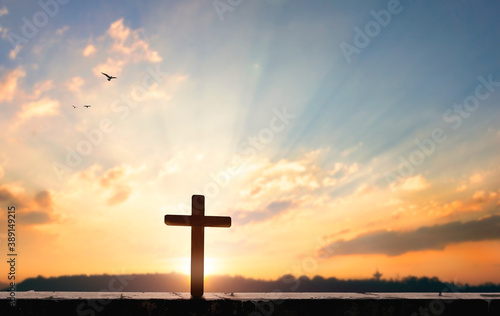 Fotografia Religious concept: Silhouette cross on  at sunset background