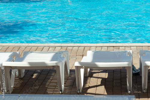 Fototapeta White sun loungers by the pool with blue bright water, copy space