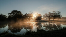 Sunbeams And Reflections On A Foggy Dawn