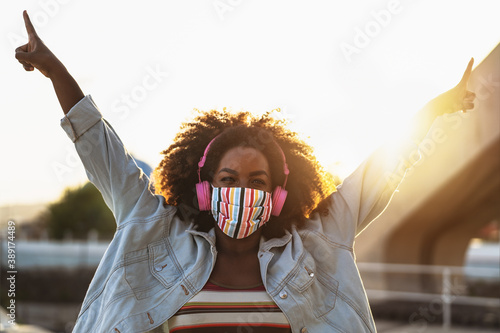 Obraz Happy Afro woman listening to playlist music with wireless headphones while wearing face colored mask outdoor - fototapety do salonu