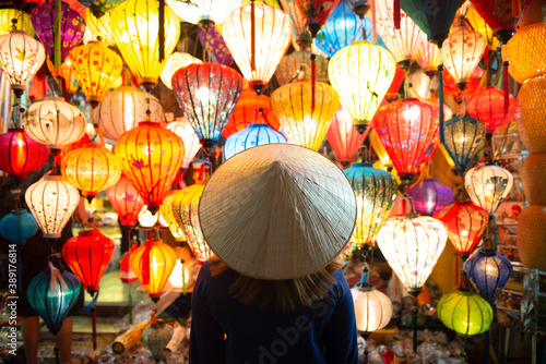 Canvastavla Tourist woman is wearing Non La (Vietnamese tradition hat) and looking colorful lanterns spread light on the old street of Hoi An Ancient Town - UNESCO World Heritage village
