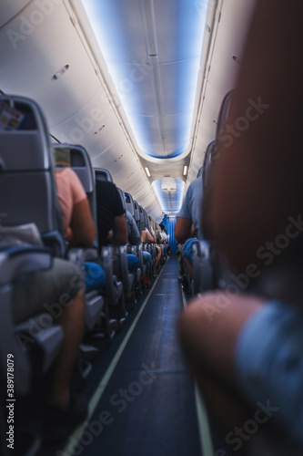 Photo Long dark corridor in the cabin of a low-cost airline - night lighting during th