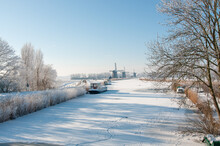 Frozen Canal With A Boat And Three Historic Windmills In A Snow Landscape In Holland