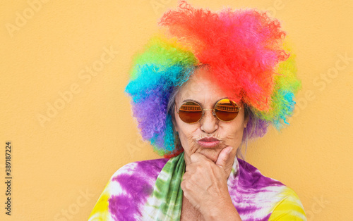 Foto Funny senior woman wearing colorful wig and sunglasses - Joyful elderly lifestyl