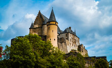 Amazing Fairy Tale Medieval European Castle On The Hill - Vianden Castle In Northern Luxembourg With Green Trees And Cloudy Skies In Summer