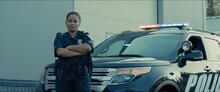 Mixed Race Female Police Officer Posing Against Police Car With Flashing Lights
