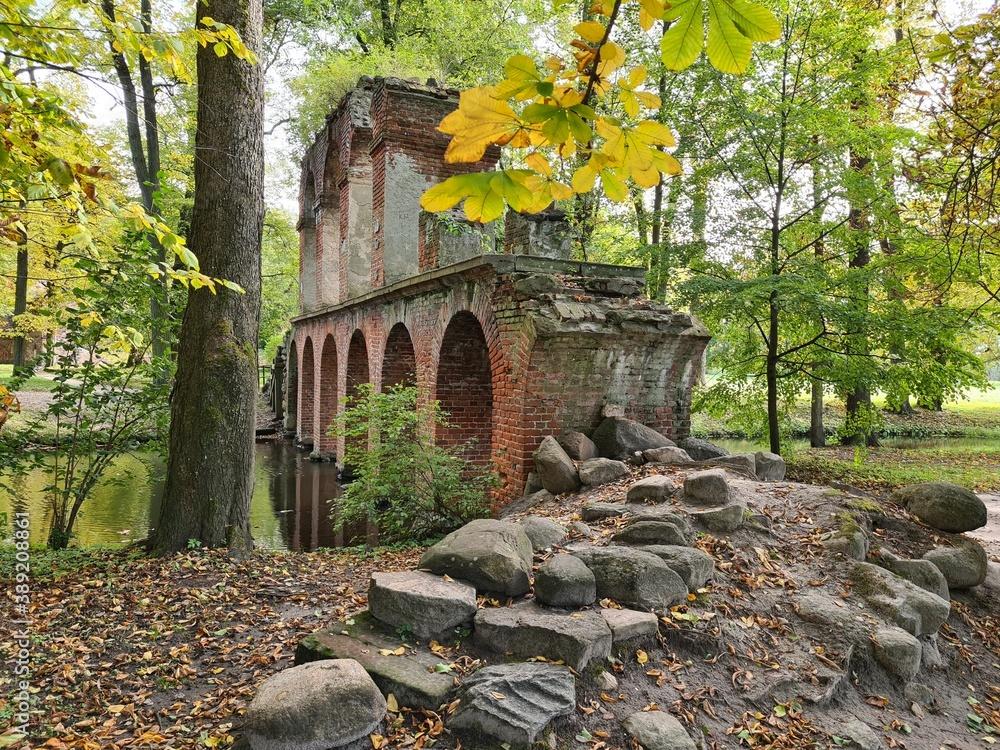 Fototapeta Zrekonstruowany akwedukt z cegieł wśród drzew w parku jesienią