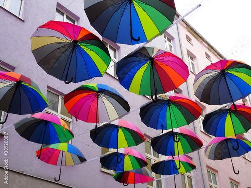 Kolorowe parasolki zawieszone między blokami wysoko nad ulicą