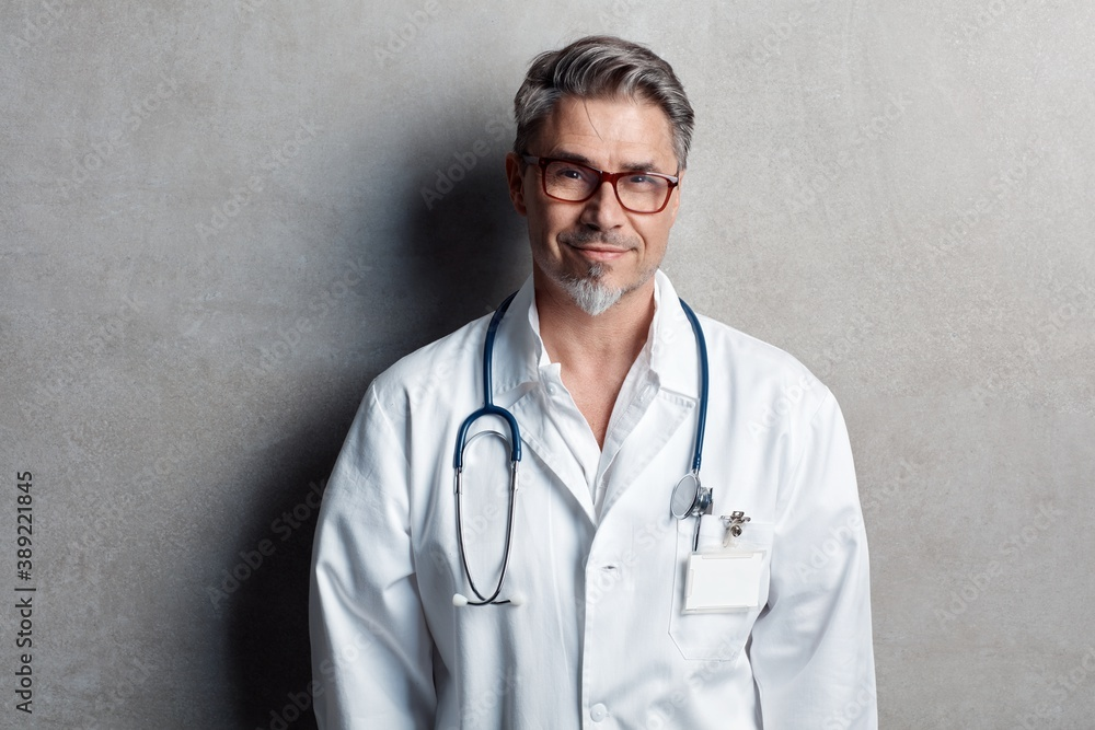 Fototapeta Portrait of trustworthy older smart doctor with gray hair wearing glasses and white lab coat standing against gray wall, smiling. Copy space.